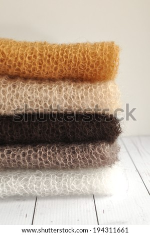Pile of soft hand knit mohair clothes  - stock photo