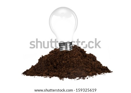 Pile of soil with light bulb, isolated on white background. - stock photo