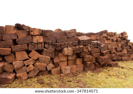 Pile of stacked bog peat turf briquette cuttings left drying in the field - stock photo