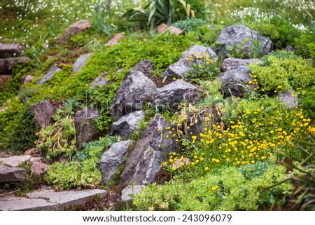Pile of stones in the green blooming garden. - stock photo