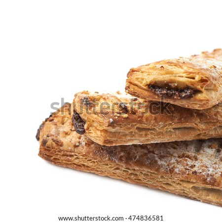 Pile of sweet chocolate pastry buns isolated over the white background, close-up crop fragment with a shallow depth of field