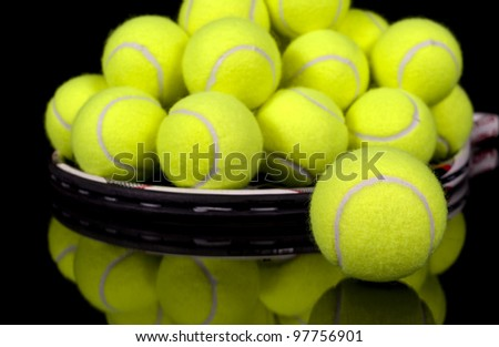 Pile of tennis balls on tennis racket isolated on black reflective surface.