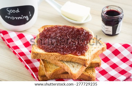 Pile of toasted bread on a kitchen table with marmalade, butter and a tea mug with good morning sign. - stock photo