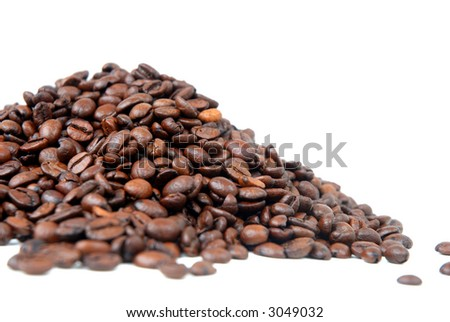 Pile of toasted coffee beans on white background