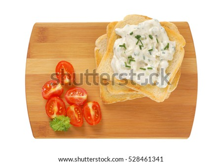 pile of toasted white bread slices, creamy chives spread on the top slice