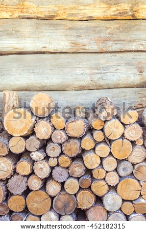 Pile of tree stumps near the timber wall, woods structure  - stock photo