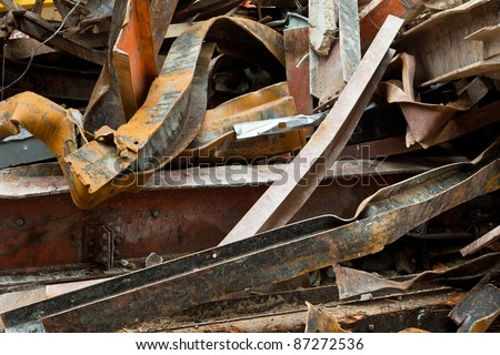 Pile of twisted and rusty scrap steel girders being recycled at a building demolition site. - stock photo