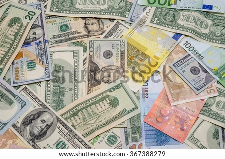 Pile of two leading currencies - US Dollar versus Euro as background - stock photo