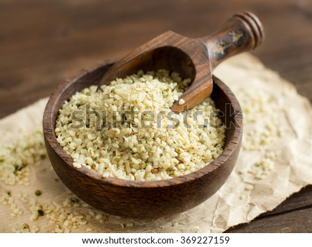 Pile of Uncooked Hemp seeds in a bowl with a spoon  - stock photo