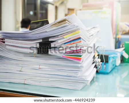Pile of unfinished paperwork on office desk - stock photo
