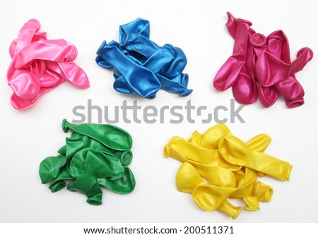 Pile of uninflated balloons from different colors. White isolated - stock photo