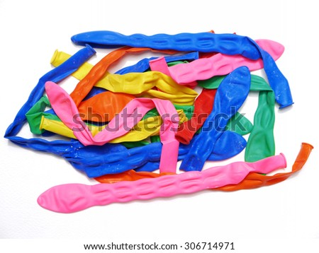 Pile of uninflated balloons from different colors. White isolated