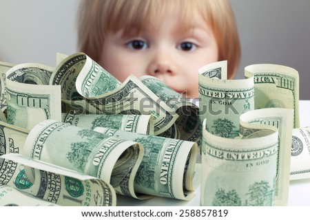 Pile of United States dollar hundred USD banknotes on white table and blurred baby looking on it on a background. Retro tonal correction photo filter effect, selective focus on money - stock photo