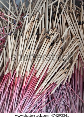 Pile of used broken off burning tips stick incense by dip in the water in Chinese shrine