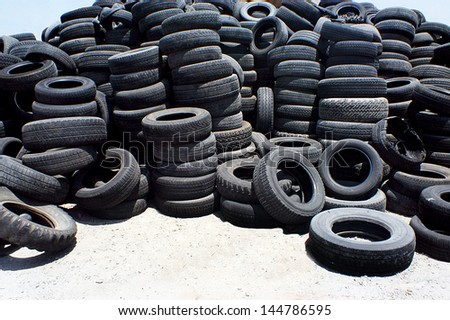 Pile of used rubber tyres in a garage back yard. - stock photo