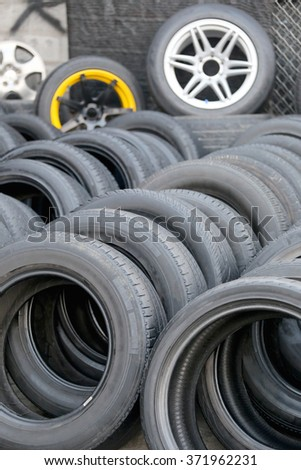 Pile of used rubber tyres in the garage shop. - stock photo