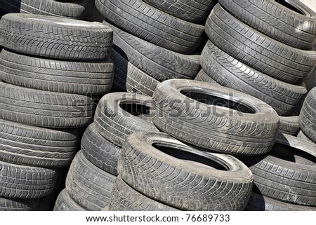 pile of used tyres on a damp - stock photo