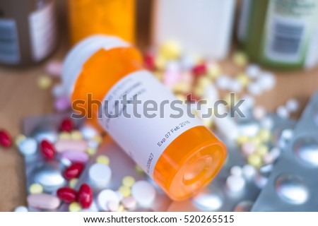 Pile of various expired prescription medicines and bottle focused on expired date. Antibiotic , paracetamol, vitamins drugs on wood background.