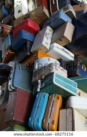 Pile of various styles of old luggage at airport or train station - stock photo