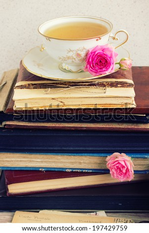 pile of vintage  books and mail with antique cup of tea - stock photo