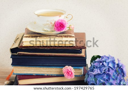 pile of vintage  books and mail with antique cup of tea and flowers - stock photo