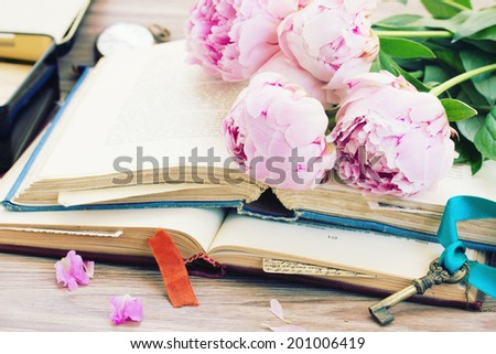 pile of vintage  books with fresh peony flowers stacked on table - stock photo