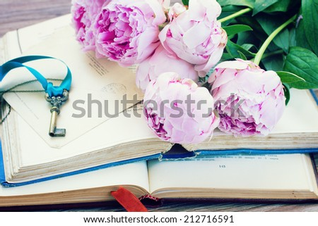 pile of vintage old books with fresh pink peony flowers stacked on table - stock photo