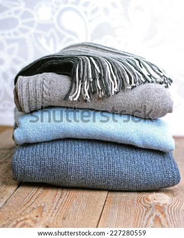 Pile of warm wool clothing lying on a wooden table - stock photo