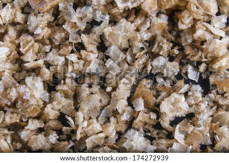 Pile of welsh oak smoked sea salt flakes on dark slate background. The salt is from Anglesey, Wales, United Kingdom, granted EU protected status in 2014. Close up. - stock photo