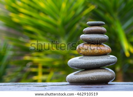 pile of wet smooth round pebbles balanced on top of  an old plank, wet from the rain with an out of focus background of yucca trees giving copy space.