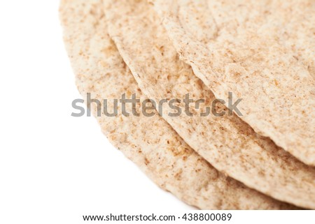 Pile of wheat tortillas isolated over the white background, close-up crop fragment as a copyspace backdrop composition - stock photo