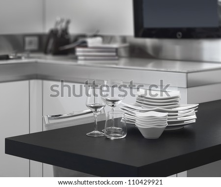 pile of white ceramic dishes on the wood worktop in a modern kitchen - stock photo