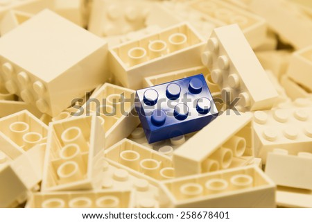 Pile of white color building blocks with selective focus and highlight on one particular blue block using available light. - stock photo