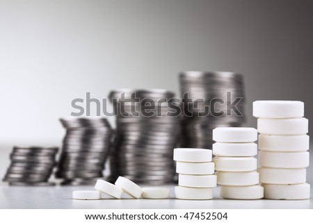Pile of white pills (in the form of a staircase) against pile of coins - stock photo