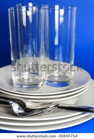 Pile of white plates, glasses with forks and spoons on silk napkin.  Focus accent on front.  Blue background - stock photo