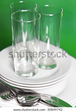 Pile of white plates, glasses with forks and spoons on silk napkin. Focus accent on front. Green background - stock photo