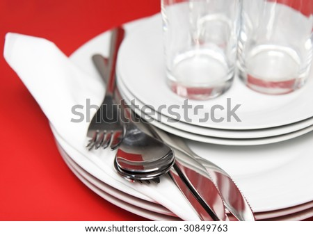 Pile of white plates, glasses with forks and spoons on silk napkin.  Focus accent on front Red background - stock photo