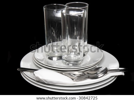 Pile of white plates, glasses with forks and spoons,silk napkin. Black   background - stock photo