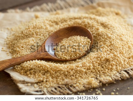 Pile of whole wheat CousCous with a spoon close up - stock photo