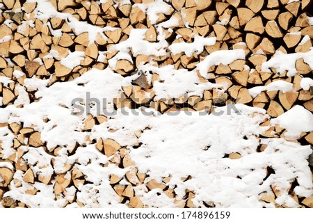 pile of wood in the snow - stock photo
