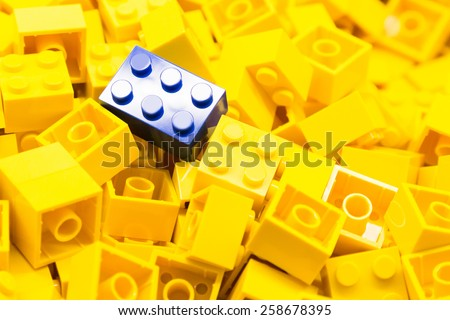 Pile of yellow color building blocks with selective focus and highlight on one particular blue block using available light. - stock photo