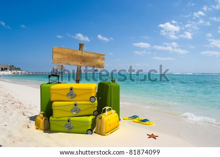 Pile of yellow luggage on a resort beach with a blank wooden sign post - stock photo