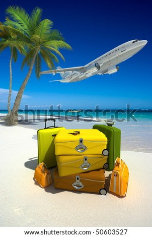 Pile of yellow luggage on a tropical beach and a flying plane - stock photo
