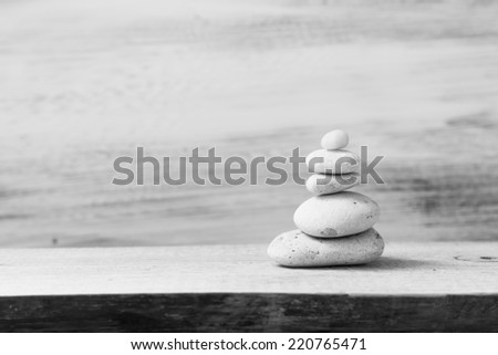 Pile of zen stones on a wooden board - stock photo