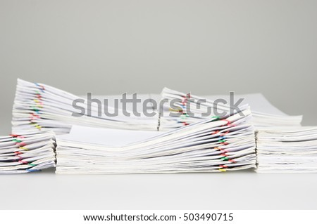 Pile overload document of receipt and report with colorful paperclip have blur pile paperwork as background on white table.