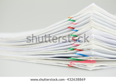 Pile overload document of report with colorful paperclip place on white background.