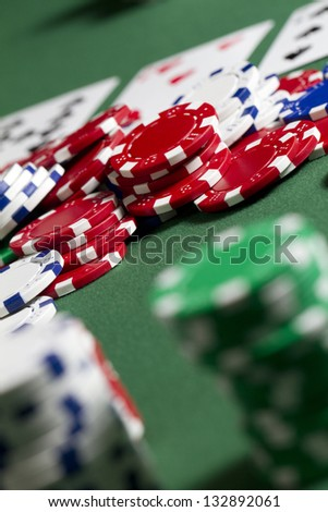 Pile Poker Chips vertical shot looking over a stack of gambling chips into the pot in the middle. shallow depth of field - stock photo