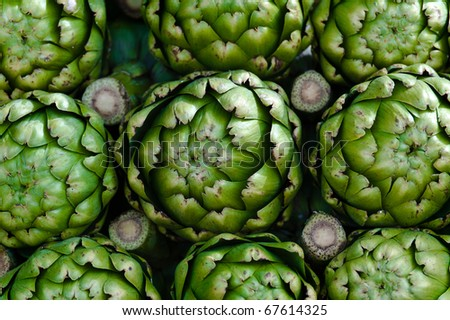 Piled artichokes in a vendor's stall at the farmers market - stock photo