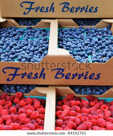 Piles of blueberries and raspberries in cardboard boxes at a farmers market