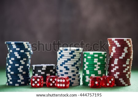 piles of casino chips with red dices on green poker table - stock photo
